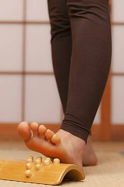 Close up young barefoot woman using foot massager in spa