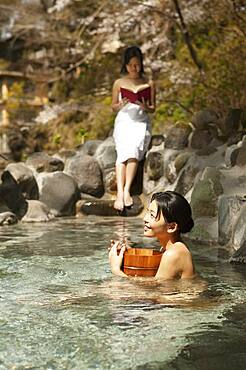 Happy young women relaxing at sunny pool in Onsen