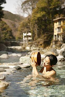 Happy young woman with bucket in sunny pool at Onsen, Izu, Japan
