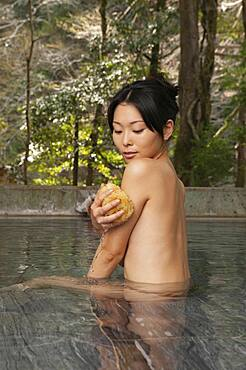 Nude young woman with loofah in tranquil Onsen pool