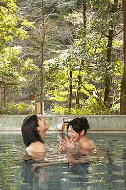 Happy young women friends soaking in pool at Onsen