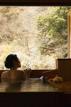 Serene young woman in Onsen pool looking out window