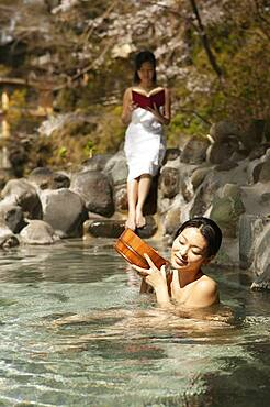 Young women relaxing and reading at sunny Onsen pool