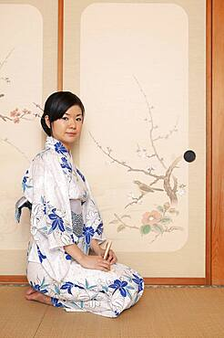 Portrait beautiful young Japanese woman in kimono at painted door