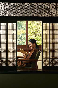 Young woman reading book in ornate shoji doorway