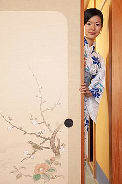 Portrait beautiful young woman in kimono behind painted door