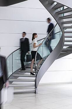 Young businesswoman ascending spiral staircase in office