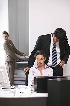 Businessman looking over shoulder of businesswoman in office