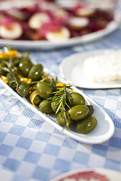 A long dish of green olives on a dining table outside