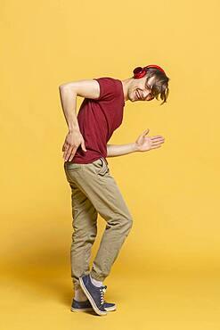 Portrait playful young man with headphones dancing