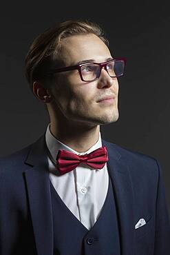 Portrait thoughtful, handsome young man in suit and eyeglasses