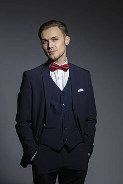 Portrait confident, handsome young man in three piece suit