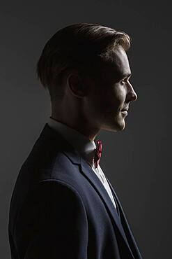 Profile portrait handsome young man in suit with bow tie