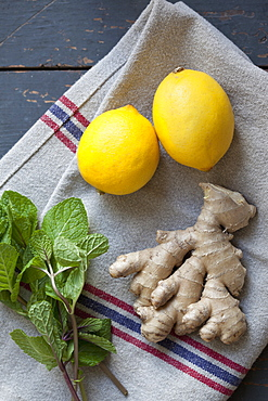 Close-up of mint leaves with ginger and lemons on napkin