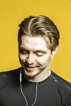 Portrait man listening to music with headphones on yellow background