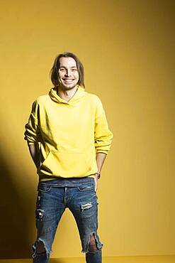 Portrait happy young man in sweatshirt and ripped jeans