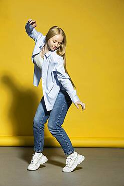 Portrait carefree young woman dancing against yellow background