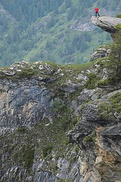 Man standing at the edge of rugged mountain cliff, Piedmont, Italy