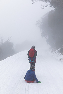 Mother pulling son on sled on snowy road