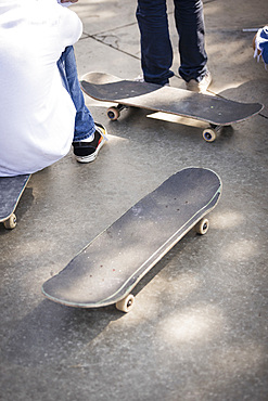 Boys with skateboards on pavement