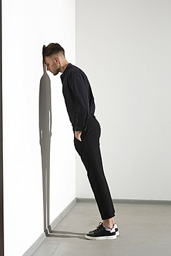 Man leaning against white wall
