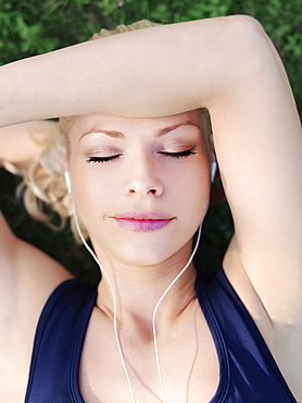 A woman wearing earphones with her eyes closed, close-up, head and shoulders