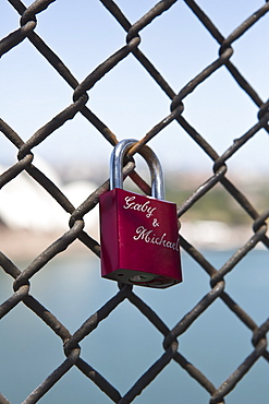 Love padlocks chainlink fence against beach