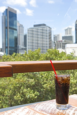 Glass of cola on table against cityscape