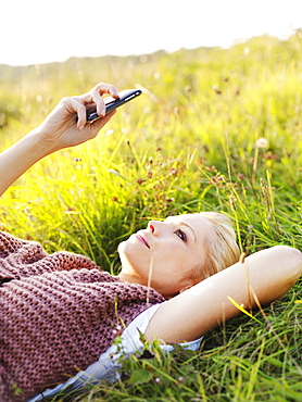 A woman lying in grass looking at her smart phone