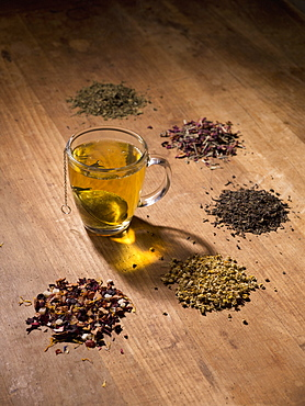Tea strainer in cup with herbs on wooden table