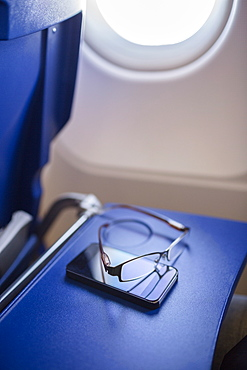 Smart phone and glasses on table in airplane
