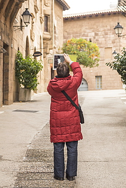 Full length of woman photographing buildings with digital tablet