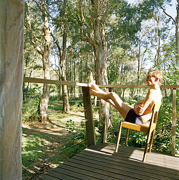 A man relaxing in a chair on a porch