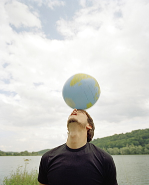 A young man balancing a ball on his head