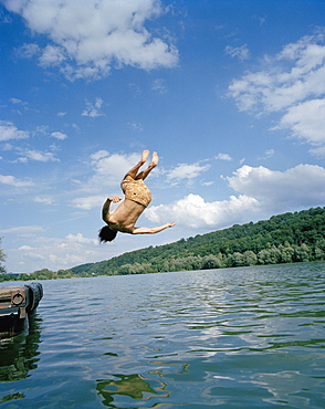A young man doing a summersault into a lake