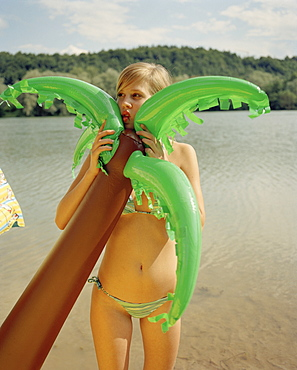 A young woman holding an inflatable palm tree by a lake