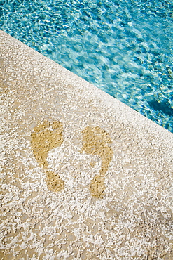 Wet footprints at the edge of a swimming pool