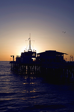 A pier in front of the sunset