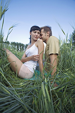 A woman teasing her boyfriend with a stalk of wheat