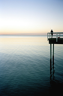 Person fishing off the end of a pier