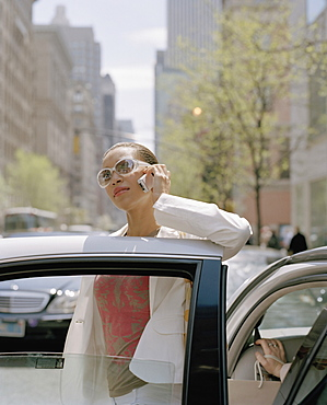 A woman stepping out of a taxi and using a mobile phone, new york city, usa
