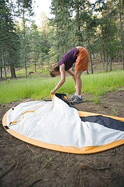 A woman setting up a tent