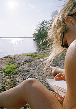 A young woman reading by a lake