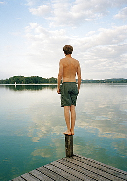 A man standing on a jetty on a lake