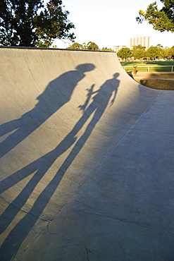 Shadows of two skateboarders on a ramp
