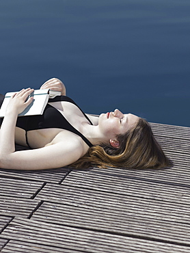 A woman lying on a jetty with an open book on her chest
