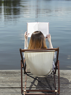 A woman sitting in a deck chair on a jetty reading a book, rear view