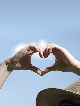 Human hands making the shape of a heart against a blue sky