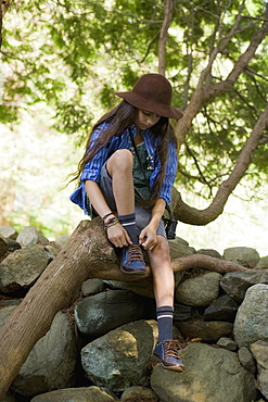 A girl sitting on a tree branch and tying her shoelace