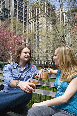 A young couple sitting on a park bench with iced coffees, central park, new york city